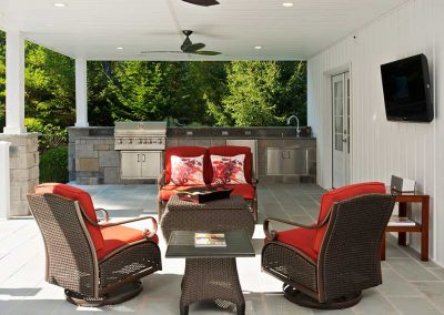 A patio built to entertain and relax. Three ceiling fans keep the air moving under this covered stone patio. Relax near the wood-burning fire or start up the grill at the outdoor kitchen.