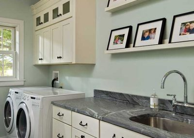 A laundry room with ample storage cabinetry and space to fold clothes.