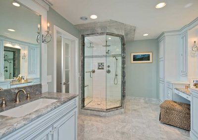 Custom cabinets with an antique painted finish, Carrara marble countertops and heated tile floors make this master bathroom bright and inviting.  Kohler steam shower with a rainfall shower head. Separate makeup vanity station.