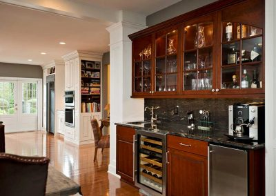 A wet bar is fitted with a wine fridge, bar sink and glass door cabinets.